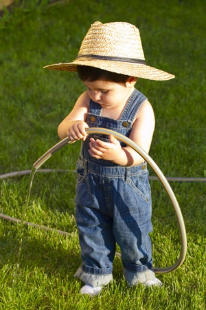 little baby boy gardener playing with water