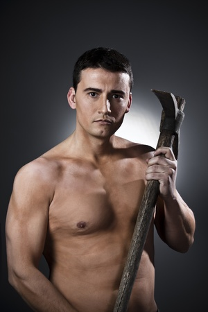 pickaxe: Young worker with pickaxe over black background