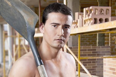 pickaxe: Serious male worker with pickaxe and bricks