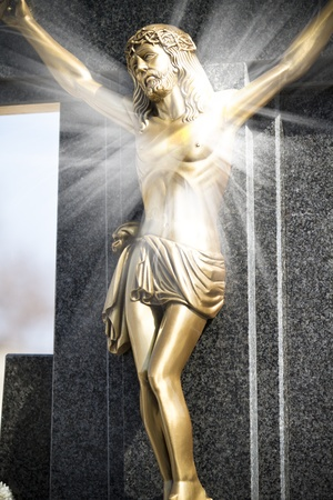 Jesus Christ on stone cross with mystic rays of light photo