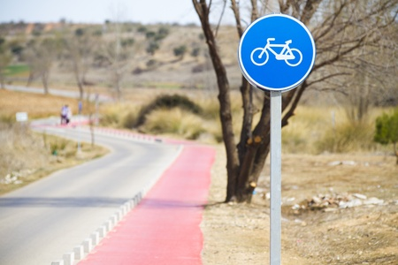bycicle: Bicycle lane with white bycicle sign, rural and natural scene