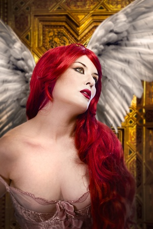 Beautiful gothic sexy angel with wings, red hair over gold background Stock Photo - 13130686