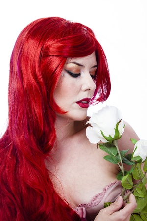 Beautiful red hair sexy woman with white rose over white background photo