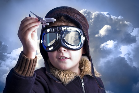 imagination: Little boy in the pilot`s hat. Boy as an old style pilot holding a toy airplane Stock Photo
