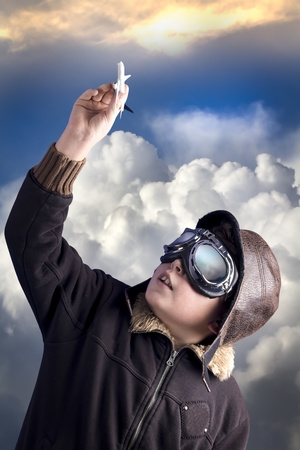 Boy as an old style pilot holding a toy airplane, heaven background Standard-Bild