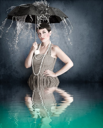 Pin-up girl with umbrella under water splash with river reflection photo