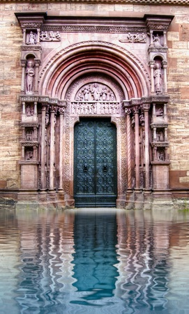 Antique cathedral gate in water reflection  Old urban architecture photo