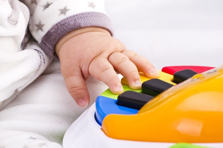 baby hand: little baby hand pianist plays on a colorful toy piano