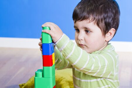 red building blocks: Brunette Baby playing with bright blocks on wooden room