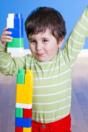 red building blocks: Baby in green shirt playing with bright blocks looking up in surprise Stock Photo