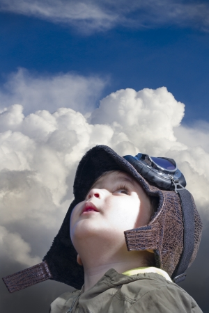 A child dressed in pilot looking into the blue sky photo