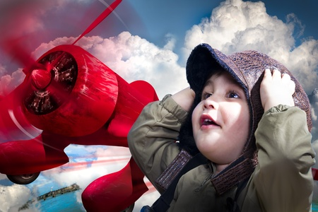 An adorable baby boy over a red planeputting his hands to his head wearing an old-fashioned pilots photo
