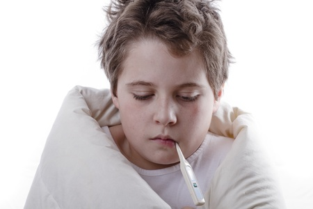 Young patient with fever, with digital thermometer and white blanket photo