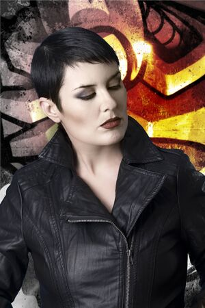 Sexy brunette young woman in a leather jacket over graffiti background with intense orange light Stock Photo - 13601252