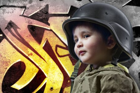 Baby playing war with military helmet against graffiti background with intense orange light photo