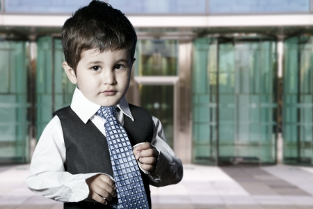 baby in suit: child dressed businessman smiling in front of building