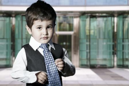 little business man: negocios ni�o vestido sonriente delante de la construcci�n de Foto de archivo