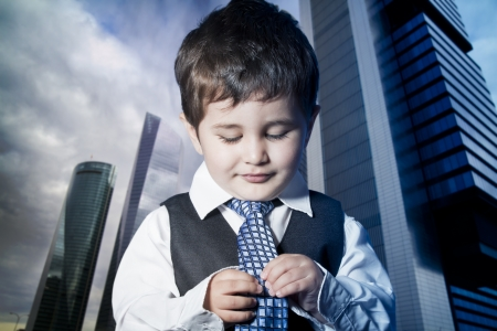 child dressed businessman with hands in his tie and skyscrapers in the background photo