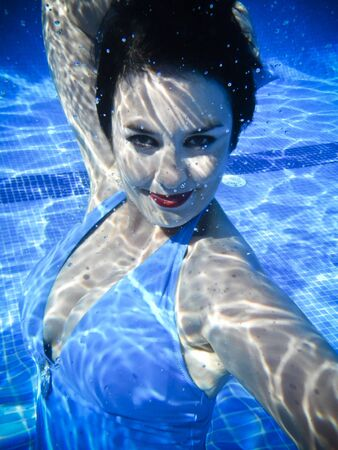 Vintage girl swimming and smiling underwater in a swimming pool photo