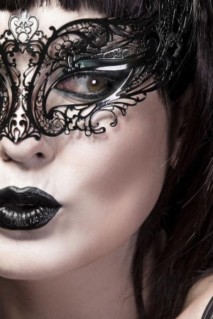 Detail of face of beautiful woman with delicate Venetian mask