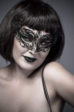 Warm woman with Venetian mask and corset, sensual, sexy and attractive photo
