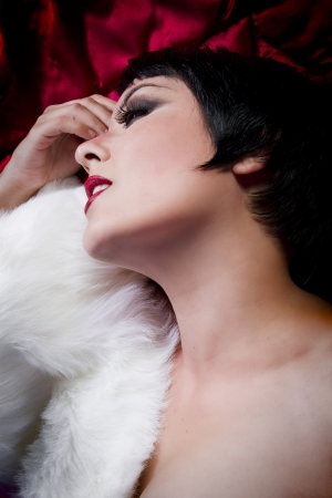 seminude: seminude beautiful short haired brunette woman lying on red silk with white fur, sensuous looking