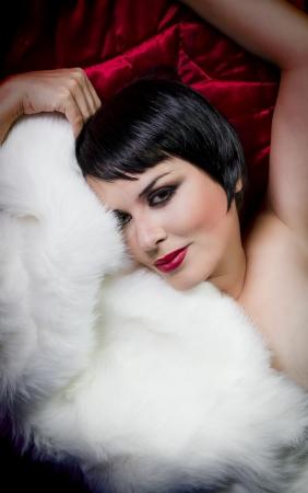 seminude: seminude bella bruna dai capelli corti donna sdraiata su seta rossa con pelliccia bianco, vecchio stile hollywood stelle