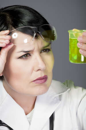 brunette female doctor checking laboratory samples with protective glasses, career women, PHD photo