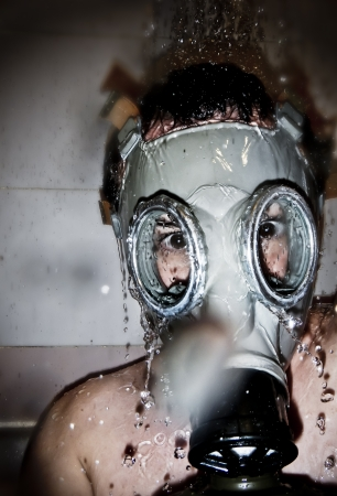 Man in gas mask with water reflection in the eyes over artistic background photo
