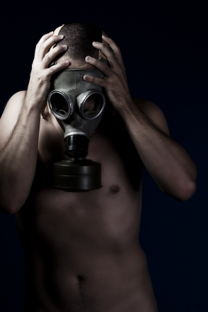 Terror, handsome man with bare torso and gas mask photo