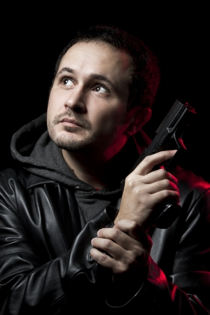 man with a gun and dressed in black leather photo