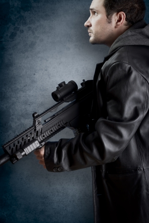 assault rifle: Man with long leather jacket and assault rifle