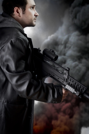 Man with long leather jacket and assault rifle, black smoke background photo