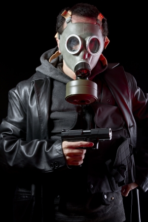 Man with gas mask and gun, dressed in black leather jacket photo