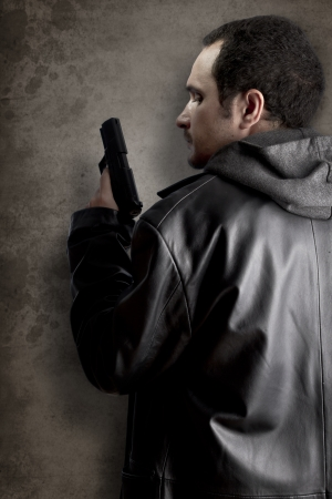 Man armed with gun on black textured background photo