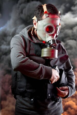 Police man with gas mask over explosion background photo