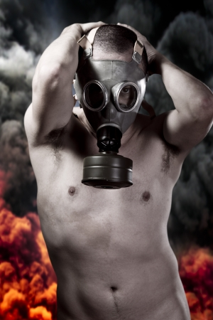 Nude man with gas mask over explosion background photo