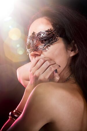 Sexy woman with  venetian mask, red light at background, shine effects photo