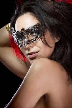 Sexy woman with  venetian mask, red light at background photo