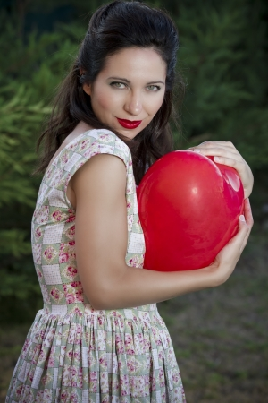 Valentines Day. Beautiful smiling woman with a gift in the form of heart in his hands, garden background photo