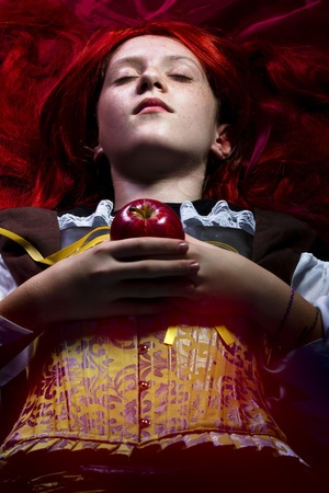 fantasy portrait of the beautiful lying Snow White with an apple photo