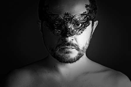 shirtless: Portrait of young man shirtless with mask against dark background.