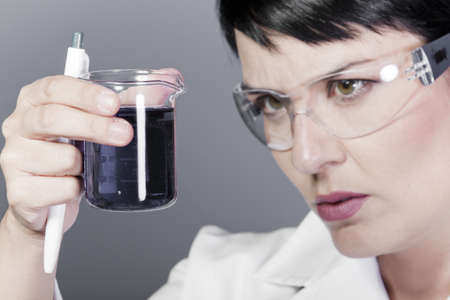 A medical or scientific researcher or doctor looking at a liquid clear solution in a laboratory. photo
