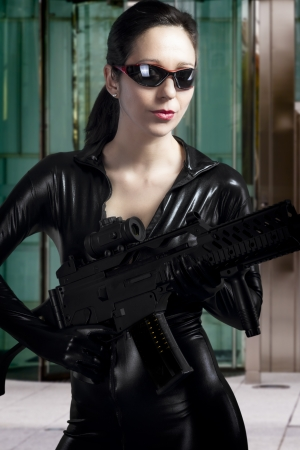Sexy beauty holding gun with business building in background photo