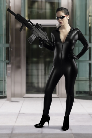 Sexy woman holding gun wearing a black leather dress photo