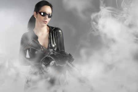 Sexy woman holding gun with helmet over smoke photo