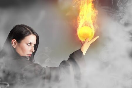 magic young: Magician woman with a fire ball in her hands
