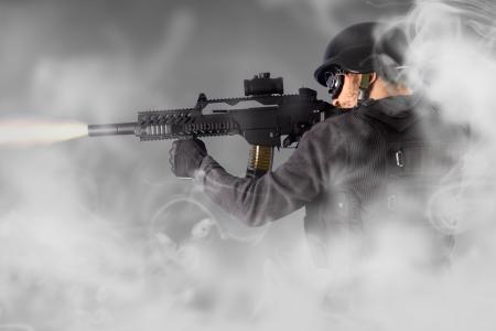 garde corps: Rue d'Assaut, police anti-�meute tirant avec son pistolet-mitrailleur, de la fum�e Banque d'images