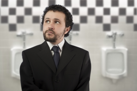 businessman with a distracted look urinating in urinals photo
