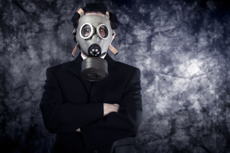 Risk concept, businessman with gas mask and black suit photo